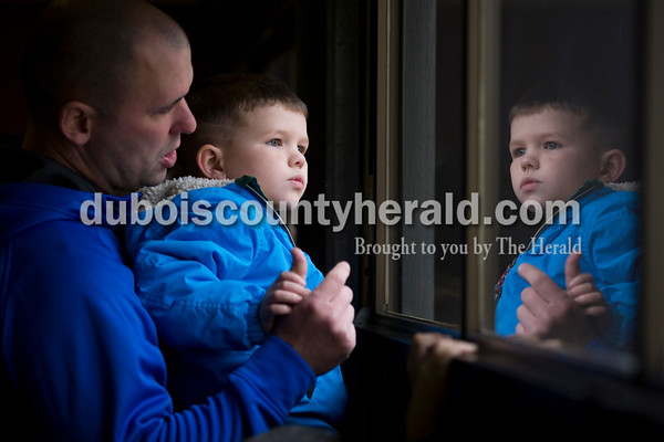 Aaron Persohn of Jasper held up his son Huck, 5, to look out at the fire trucks from inside the Jasper Fire Station after visiting with Santa on Friday. Sarah Ann Jump/The Herald