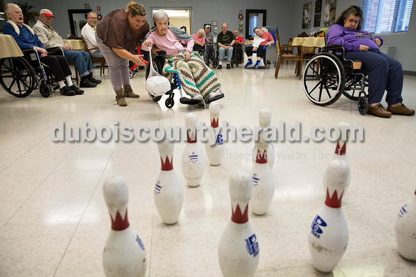 Sarah Ann Jump/The Herald Activities director Kim Robbins, left, assisted resident Beulah Howell in rolling a frozen 13-pound turkey during turkey bowling on Wednesday morning at Cathedral Health Care Center in Jasper.