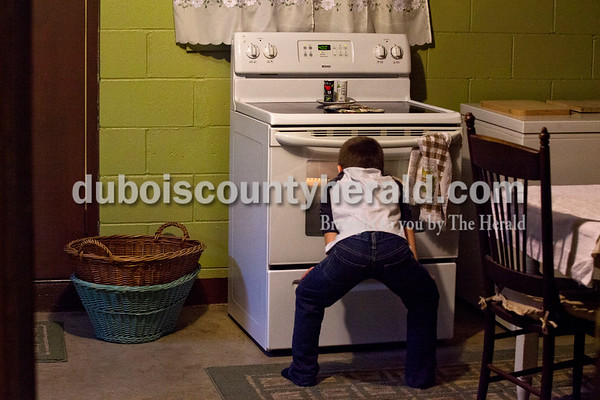 Marshall Schepers, 7, checked to see if the first round of pies were done baking on Wednesday evening at his grandmother's home in Dubois.    Alisha Jucevic/The Herald