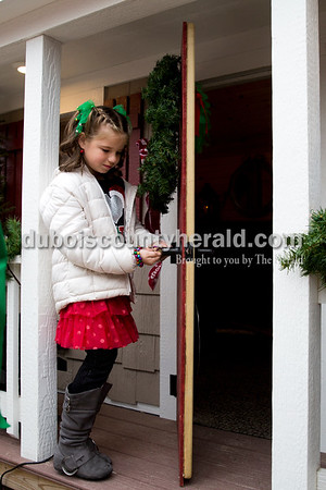 Reagan Hopf of Ireland, 8, unlocked the door to Santa's new house on the Square in Jasper on Friday. Reagan, a second-grader at Ireland Elementary, won a coloring contest that gave her the honor of helping to dedicate the house and light the Christmas tree. Sarah Ann Jump/The Herald