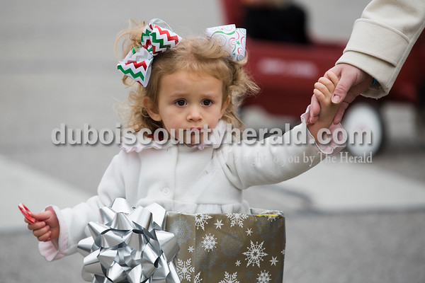 Lily Schnarr of Jasper, 2, held her mother Brooklyn Schnarr's hand as she paraded from the Jasper Fire Station to Santa's new house on the Square in Jasper on Friday. Sarah Ann Jump/The Herald
