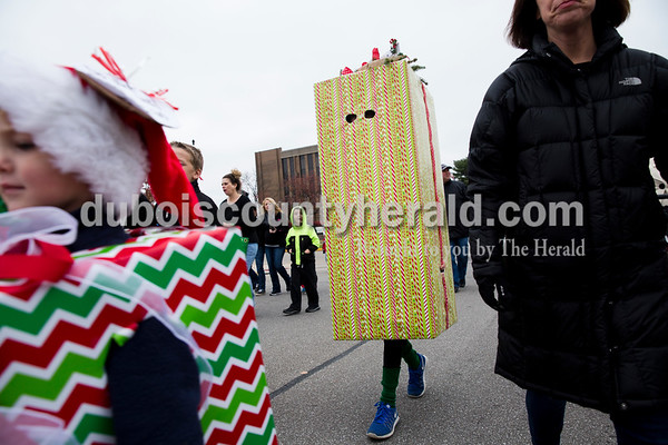Mason Thornburgh of Jasper, 11, center, wore a tall box wrapped in gift wrap as he paraded from the Jasper Fire Station to Santa's new house on the Square in Jasper on Friday. Sarah Ann Jump/The Herald