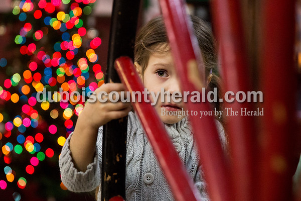 Elin Ruhe of Jasper, 4, spun the wheel to an antique chemical engine, used to extinguish fires before motorized fire engines, after visiting with Santa at the Jasper Fire Station on Friday. Sarah Ann Jump/The Herald