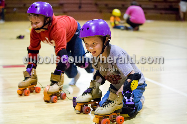 Sarah Ann Jump/The Herald Holland Elementary School second-graders William Sickbert, left, and Jeffery Owens, rolled their skates back to the storage area after learning to roller skate in physical education class at the school on Wednesday.