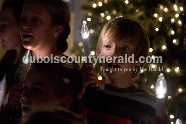 "Sarah Shaw/The Herald Jaxson Flamion of Holland, 8, sang ""O Holy Night"" with the youth choir during an advent candlelight service Sunday night at St. James Lutheran Church in Holland. A freewill offering was designated for the family of Kathy Buse of Santa Claus, who has been affected by cancer."