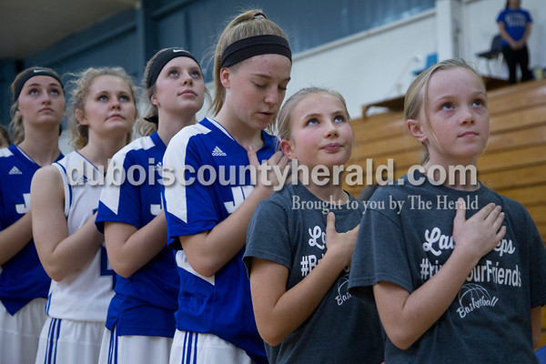 Allie Knies, right, and Cassidy Riecker, both 10 and of Celestine, stood with the Jeeps for the national anthem during Thursday's game against Springs Valley in Dubois. The girls watched the game from the bench and hung out with the team in the locker room as a reward for working hard in school. The Jeeps won 49-45.  Sarah Shaw/The Herald