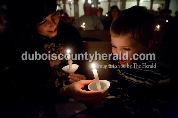 Sarah Shaw/The Herald Ethan Minihan of Grand Rivers, Ky., 4, held a candle with help from his mother and Holland-native Sara during an advent candlelight service Sunday night at St. James Lutheran Church in Holland. A freewill offering was designated for the family of Kathy Buse of Santa Claus, who has been affected by cancer.