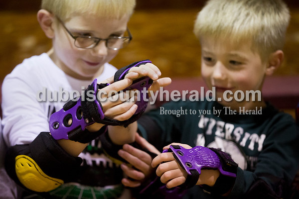 Sarah Ann Jump/The Herald Holland Elementary School first-graders Maverick Wright, left, and Gage Sherman inspected the wrist guards that students wore as they learned to roller skated in physical education class at the school on Wednesday. In addition to wrist guards, each student wore knee pads, elbow pads and a helmet.