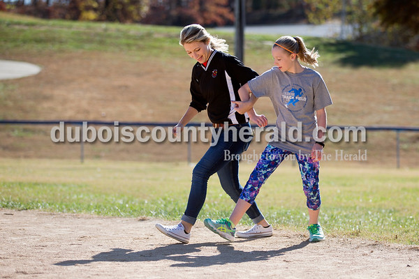 Sarah Ann Jump/The Herald Northeast Dubois High School sophomore Brooklyn Dodd, a peer mentor, left, and Dubois Middle School sixth-grader Emma Schneider skipped towards the kickball field after lunch at the middle school on Friday.