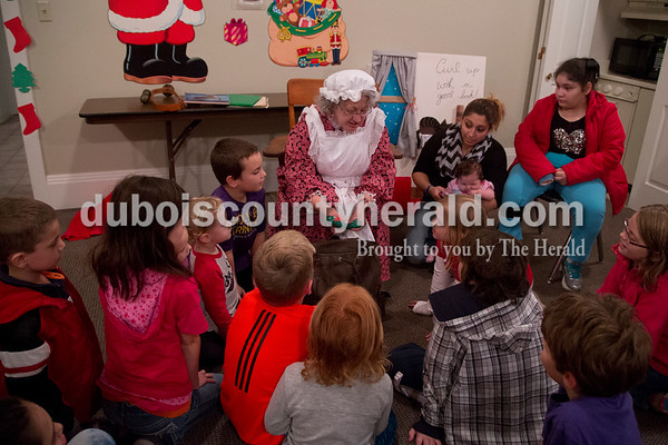 Sarah Shaw/The Herald Mrs. Claus borrowed one of Santa's bags to show audience members during a Letters to Santa Workshop at the Jasper Public Library on Tuesday evening. Mrs. Claus visited the library to share tales from the North Pole and help children write letters to Santa.