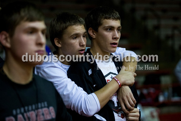 Southridge High School seniors Chase Stetter, left, Braden Harding, and Matthew Price watched the final moments of action as the Raiders lost Tuesday night's game at Memorial Gymnasium in Huntingburg. The Rangers defeated the Raiders 35-33.   Alisha Jucevic/The Herald