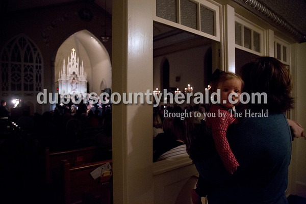 Sarah Shaw/The Herald Beth Meyer of Holland held 9-month-old Lydia Blackgrove of Holland during an advent candlelight service Sunday night at St. James Lutheran Church in Holland. A freewill offering was designated for the family of Kathy Buse of Santa Claus, who has been affected by cancer.