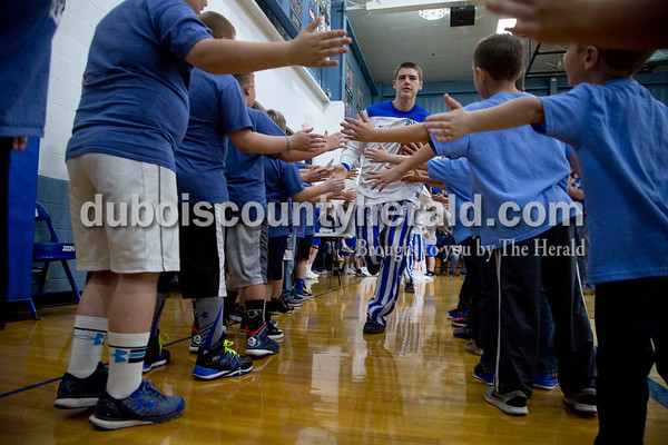 Northeast Dubois' Scott Betz sprinted through a tunnel of youth basketball players before the start Saturday's game against Tell City in Dubois. The Jeeps won 34-29.  Sarah Shaw/The Herald