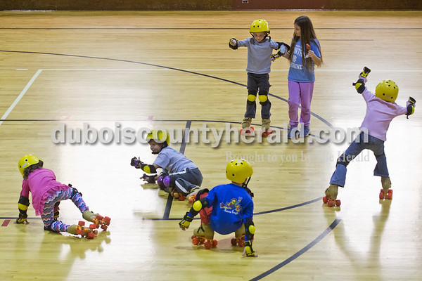 Sarah Ann Jump/The Herald Holland Elementary School first-grader Matthew Hampton, top left, received assistance from third-grader Jaylynn Goodwin as the first grade students learned to roller skate in physical education class at the school on Wednesday.