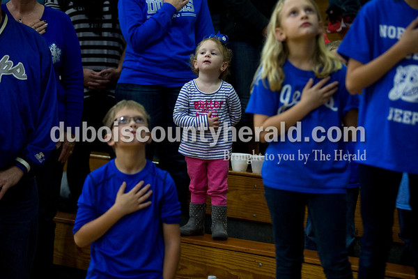 Ashtyn Kalb of Dubois, 2, stood in-between her cousin Bodie Pieper, 8, left, and sister Adalie, 8, during the national anthem before Friday night's game against Washington Catholic in Dubois. The Jeeps defeated the Cardinals 54-15.  Alisha Jucevic/The Herald