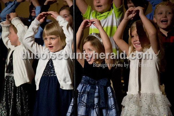 Sarah Shaw/The Herald Trinity Darling of Holland, 5, left, Adalyn Blessinger of Huntingburg, 4, and Amelia Kirk of Holland, 4, sang during an advent candlelight service Sunday night at St. James Lutheran Church in Holland. A freewill offering was designated for the family of Kathy Buse of Santa Claus, who has been affected by cancer.