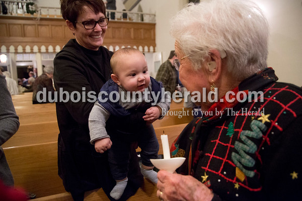 Sarah Shaw/The Herald Sara Prusz of Holland, left, held her 7-month-old grandson Ian Mathies of Huntingburg to greet his great-grandmother Melba Prusz of Holland, following an advent candlelight service Sunday night at St. James Lutheran Church in Holland. A freewill offering was designated for the family of Kathy Buse of Santa Claus, who has been affected by cancer.