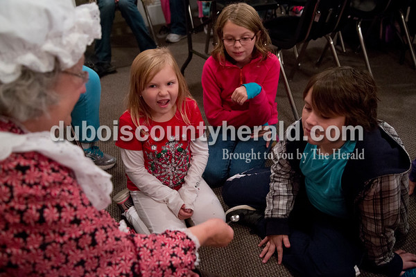 Sarah Shaw/The Herald Madalyn Breeding of Jasper, 7, left, Winnie Jackson of Jasper, 7, and Reuben Harker of Jasper, 11, reacted as Mrs. Claus showed an elf an elf spoon during a Letters to Santa Workshop at the Jasper Public Library on Tuesday evening. Mrs. Claus visited the library to share tales from the North Pole and help children write letters to Santa.