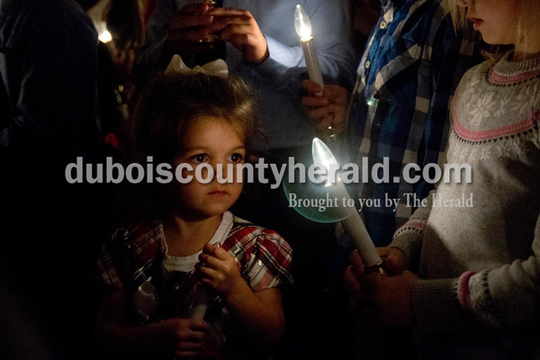 Sarah Shaw/The Herald Ellington Flamion of Holland, 2, held a candle while performing with the cherub choir during an advent candlelight service Sunday night at St. James Lutheran Church in Holland. A freewill offering was designated for the family of Kathy Buse of Santa Claus, who has been affected by cancer.