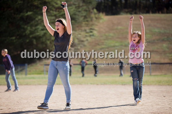 Sarah Ann Jump/The Herald Northeast Dubois High School sophomore Addison Kirchoff, a peer mentor, left, and Dubois Middle School fifth-grader Amya Hambrick celebrated an out during a kickball game after lunch at the middle school on Friday.
