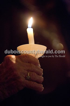 Sarah Shaw/The Herald Melba Prusz of Holland held a candle during an advent candlelight service Sunday night at St. James Lutheran Church in Holland. A freewill offering was designated for the family of Kathy Buse of Santa Claus, who has been affected by cancer.