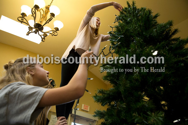 Sarah Ann Jump/The Herald Jasper Middle School seventh-graders Leslie Mendel, left, and Mackenzie Belk strung lights on a Christmas tree at St. Charles Health Campus in Jasper on Thursday.