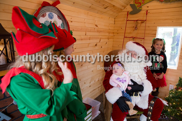 Five-month-old Olivia Hellman of Chicago looked over at elves Andyn Lampert, left, and Lauren Mundy, both 8 and of Ireland, as she visited with Santa in his new house on the Square in Jasper on Friday. Reagan Hopf of Ireland, 8, right, helped hand out candy canes. Olivia's father Nick Hellman is a Jasper native that was in town visiting family for Thanksgiving. Sarah Ann Jump/The Herald