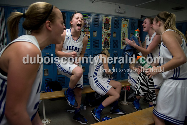 Northeast Dubois' Jessica Kahle, left, and Clare Mangin celebrated with their teammates in the locker room following Thursday's game against Springs Valley in Dubois. The Jeeps won 49-45.  Sarah Shaw/The Herald