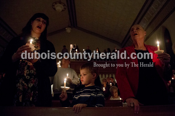 "Sarah Shaw/The Herald Sara Minihan of Grand Rivers, Ky., left, her son Ethan, 4, and her mother Martha Krohn of Princeton sang ""Silent Night"" during an advent candlelight service Sunday night at St. James Lutheran Church in Holland. A freewill offering was designated for the family of Kathy Buse of Santa Claus, who has been affected by cancer."