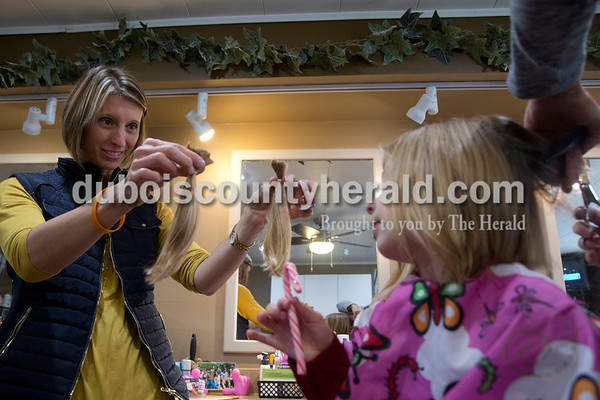 Sarah Shaw/The Herald Celestine native Kami Reuter of Pittsboro showed her daughter Ali, 4, the eight inches of hair that she had cut at Family Hair Fashions in Jasper on Saturday. Ali got eight inches of hair cut in order to donate to Children with Hair Loss, a non-profit based in Michigan that makes wigs for children who have lost their hair to cancer. Ali's older brother Bodie, 6, is currently battling acute lymphoblastic leukemia at Riley Hospital for Children. Ali wanted to donate her hair in honor of her older brother and to support other little boys and girls battling cancer. The family traveled to Jasper so that Shelly Main, who cut Kami's hair as a child, could do the honors.