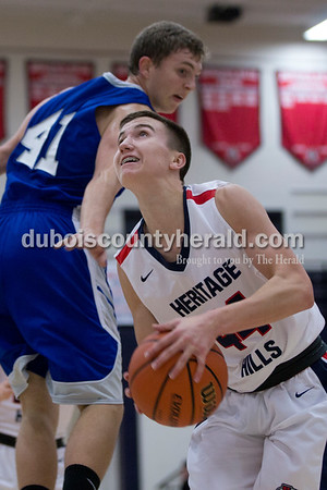Heritage Hills' Murray Becher eyed the basket while Northeast Dubois' Chase Riecker defended during Saturday's game against Northeast Dubois in Lincoln City. The Patriots defeated the Jeeps 43-36.  Sarah Shaw/The Herald