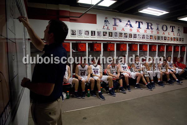 The Heritage Hills Patriots listened as head coach Nate Hawkins outlined a play during halftime of Saturday's game against Northeast Dubois in Lincoln City. The Patriots defeated the Jeeps 43-36.  Sarah Shaw/The Herald