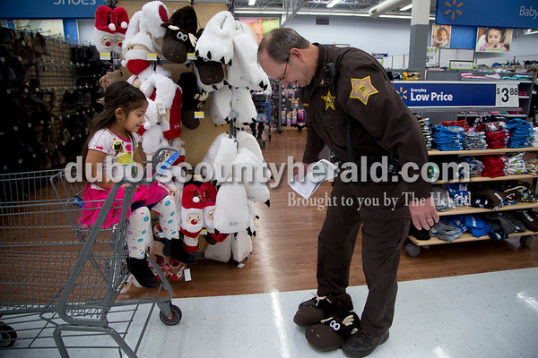 Sarah Shaw/The Herald Dubois County Sheriff Lt. Tim Lampert pretended to try on moose slippers while shopping with Alexia, 3, during the annual Tri-Cap Head Start Cops and Kids event this morning at Walmart in Jasper. Around 60 Dubois County children were paired local law enforcement members to shop for gifts.