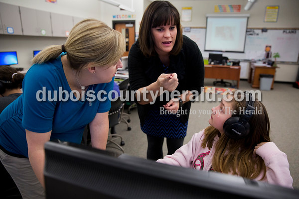 "Sarah Ann Jump/The Herald Jasper Middle School computer instructor Lindsey Smith, left, and eLearning Coach Dana Kunz explained the ""Hour of Code"" program to sixth-grader Desiree Wagner at the school on Monday, the first day of Computer Science Education Week."