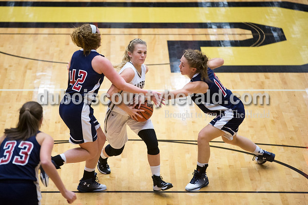 Jasper's Madisyn Hunt pushed her way through Heritage Hills' Sydney Scherry and Kerragan Mulzer, causing her to lose control of the ball, during Tuesday's girls basketball game in Jasper. Heritage Hills defeated Jasper 67-60. Sarah Ann Jump/The Herald