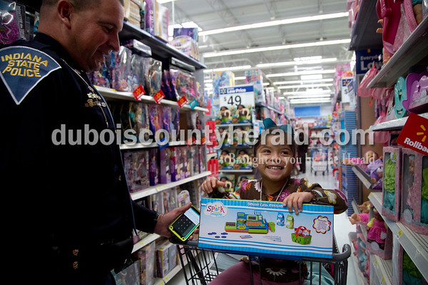 Sarah Shaw/The Herald Indiana State Police Sgt. Aaric Correll helped Lezly, 4, pick out a toy cash register during the annual Tri-Cap Head Start Cops and Kids event this morning at Walmart in Jasper. Around 60 Dubois County children were paired local law enforcement members to shop for gifts.