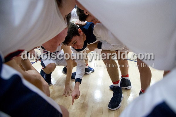 "Heritage Hills' Gabe Hitz told his teammates this is ""Our Court"" in a huddle before Saturday's game against Northeast Dubois in Lincoln City. The Patriots defeated the Jeeps 43-36.  Sarah Shaw/The Herald"