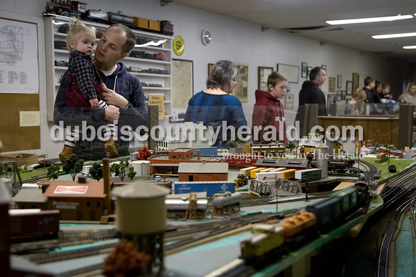Sarah Shaw/The Herald Isabeau Jones of Jasper, 1, and her father Josh inspected a model train layout during the Model Train Show at the Dubois County Museum in Jasper on Saturday. The show featured over 20 vendors selling different types and sizes of train cars, sets, toys and accessories, as well as several train layouts throughout the museum.