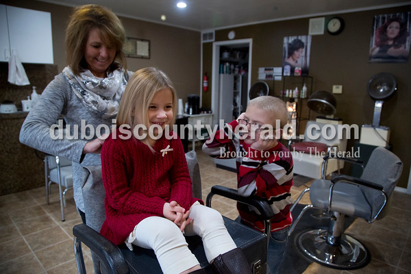 Sarah Shaw/The Herald Bodie Reuter of Pittsboro, 6, right, watched as Shelly Main of Jasper prepared to cut his four-year-old sister Ali's hair at Family Hair Fashions in Jasper on Saturday. Ali got eight inches of hair cut in order to donate to Children with Hair Loss, a non-profit based in Michigan that makes wigs for children who have lost their hair to cancer. Bodie is currently undergoing chemotherapy treatment for acute lymphoblastic leukemia at Riley Hospital for Children. While some of Bodie's hair is growing back, Ali wanted to donate her hair to support other little boys and girls battling cancer. The family traveled to Jasper so that Main, who cut the hair of Ali's and Bodie's mother Celestine native Kami (Vaal) as a child, could do the honors.