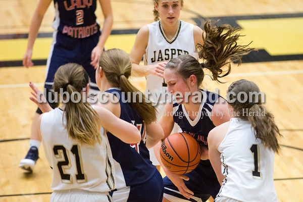 Heritage Hills' Abby Wahl and other players struggled to gain possession of the ball during Tuesday's girls basketball game in Jasper. Heritage Hills defeated Jasper 67-60. Sarah Ann Jump/The Herald