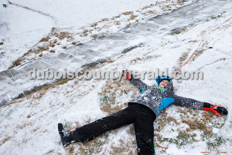 Spencer Baugh of Jasper, 9, made a snow angel this morning outside his home in Jasper. Snow began to fall early this morning, and all four Dubois County school districts called off classes. <br /> <br /> Alisha Jucevic/The Herald