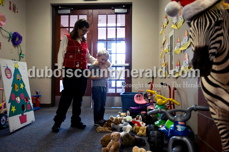 "Brenda Mangel of Holland helped preschooler Torrin Ellis pick out a stuffed animal in the hallway during the class Christmas party on Dec. 21 at Holland Elementary School. Mangel use to work as a substitute educational assistant, but when the system changed to eliminate subs for assistants, she found other ways to still help the children and make regular visits. On Easter and Christmas Mangel brings stuffed animals for the children and on Halloween they stop by her house for trick-or-treating to pick up a bag of goodies. Preschool teacher Vicki Schulthise said she also brings by extra clothes for the students that they can use if they get dirty, or kids games that she finds almost brand new at yard sales. ""We use to laugh, every time someone (an assistant) is absent or something chaotic happened, she shows up,"" said Schulthise. ""She's an amazing help and shows up at the right time."" <br /> Alisha Jucevic/The Herald"