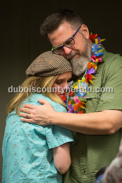 "Sarah Ann Jump/The Herald<br /> Jasper-native Chelsea Gill of Los Angeles was comforted by Jim Ansaldo of Bloomington during a luau-themed celebration of life in memory of Chelsea's father Colin Gill at the Jasper Arts Center on Wednesday. Chelsea said the luau reflected her father's personality and his wishes for a celebration. ""He was full of character,"" said Megan Gill, Chelsea's twin sister, of their father. ""He was a total goof ball. He brought the personality and spirit to everything."""