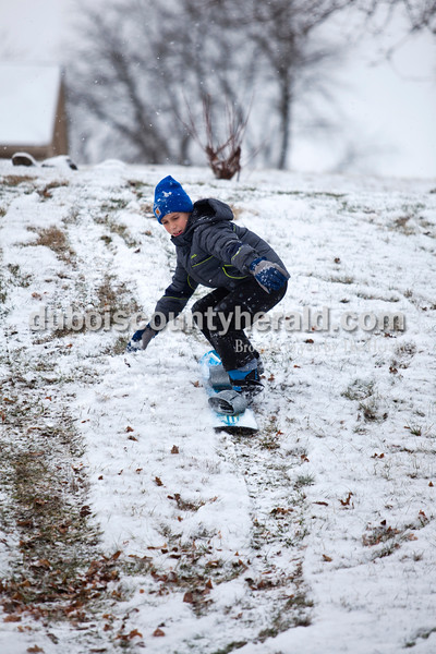 Ayden Dale of Jasper, 10, tried out his friend's snowboard this morning in Jasper. Snow began to fall early this morning, and all four Dubois County school districts called off classes. <br /> <br /> Alisha Jucevic/The Herald