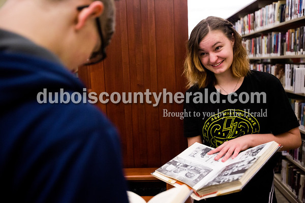 Tegan Johnston/The Herald Laney Vaughn of Birdseye, 13, looked through books with Garrett Debevoise of Ferdinand, 13, at Ferdinand Public Library on Thursday afternoon while avoiding the rain. Vaughn and Debevoise go to the library a couple times a week to hang out after school.