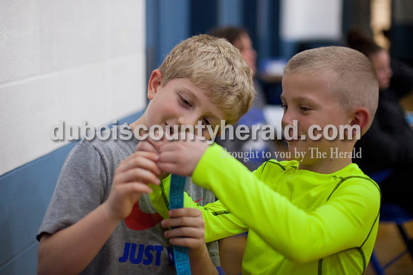 Northeast Dubois fans Dustin Riecker of Celestine, 8, left, and Carter Fuhs of Dubois, 7, counted Dustin's raffle tickets during Friday night's game against Paoli in Dubois. The Jeeps lost 60-51.  Alisha Jucevic/The Herald