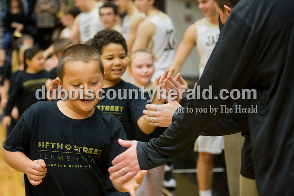 Fifth Street Elementary first-grader Reese Weisheit of Jasper, 7, high-fived the Jasper basketball team players and coaches after singing the national anthem with his classmates before Saturday's basketball game in Jasper. Jasper defeated Southridge 57-52. Sarah Ann Jump/The Herald