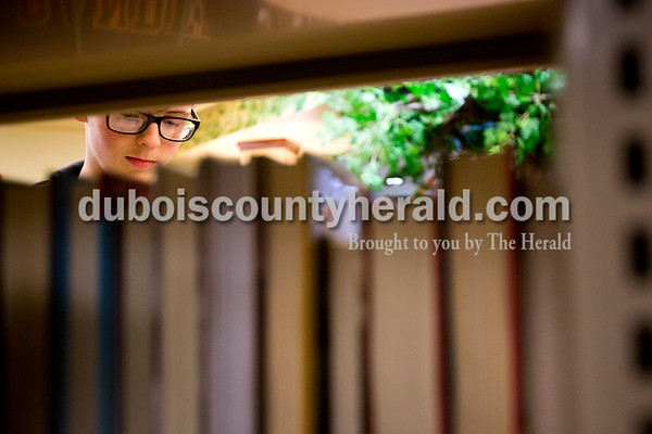 Tegan Johnston/The Herald Garrett Debevoise of Ferdinand, 13, spent the afternoon browsing through books at the Ferdinand Public Library on Thursday while avoiding the rain. Debevoise said he comes to the library a couple times a week to hang out after school.