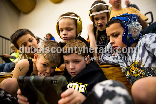 Tegan Johnston/The Herald Nolan Mullins, 8, held the iPad as his friends, from left clockwise, Landon Martindale, 6, Brayden Benton, 8, Donovan Pauw, 8, Jude Peter, 9, and Mason Bower, 7, all from Jasper, gathered around him during the 41st annual Folkstyle Open wrestling tournament at Jasper Middle School on Sunday. Children in age divisions pee wee through cadet competed in the event.
