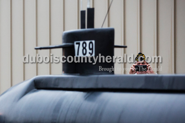Sarah Ann Jump/The Herald American Legion Post 147 Commander Pat Moriarty of Portersville photographed a 16-foot model of the USS Indiana outside of the American Legion Hall in Jasper on Tuesday.